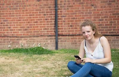 A girl sits outside looking for advice on her phone. Centrepoint provides legal advice for homeless young people.