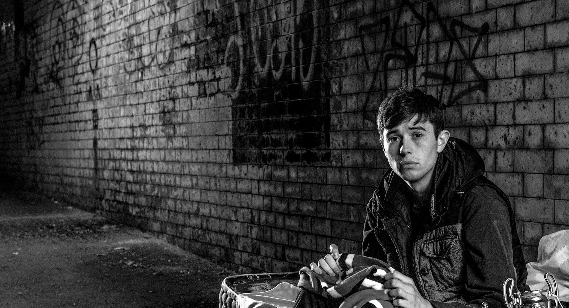 Young man sitting alone on a mattress on a dimly lit street