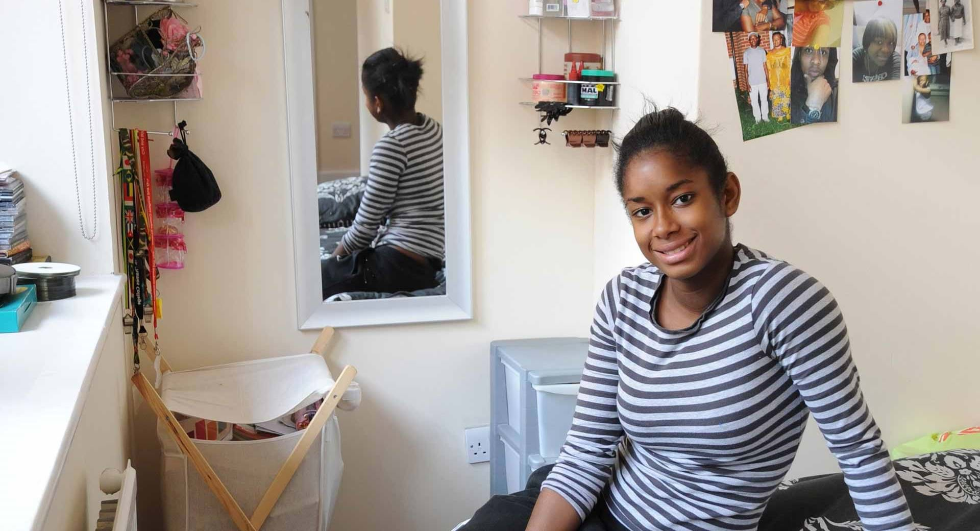 Smiling young woman in a room provided by Centrepoint's housing services