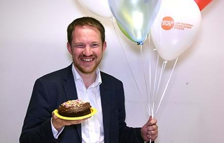 Man in suit holds cake and balloons.