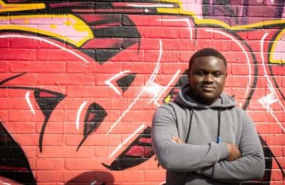 A young man stands in front of a graffiti wall