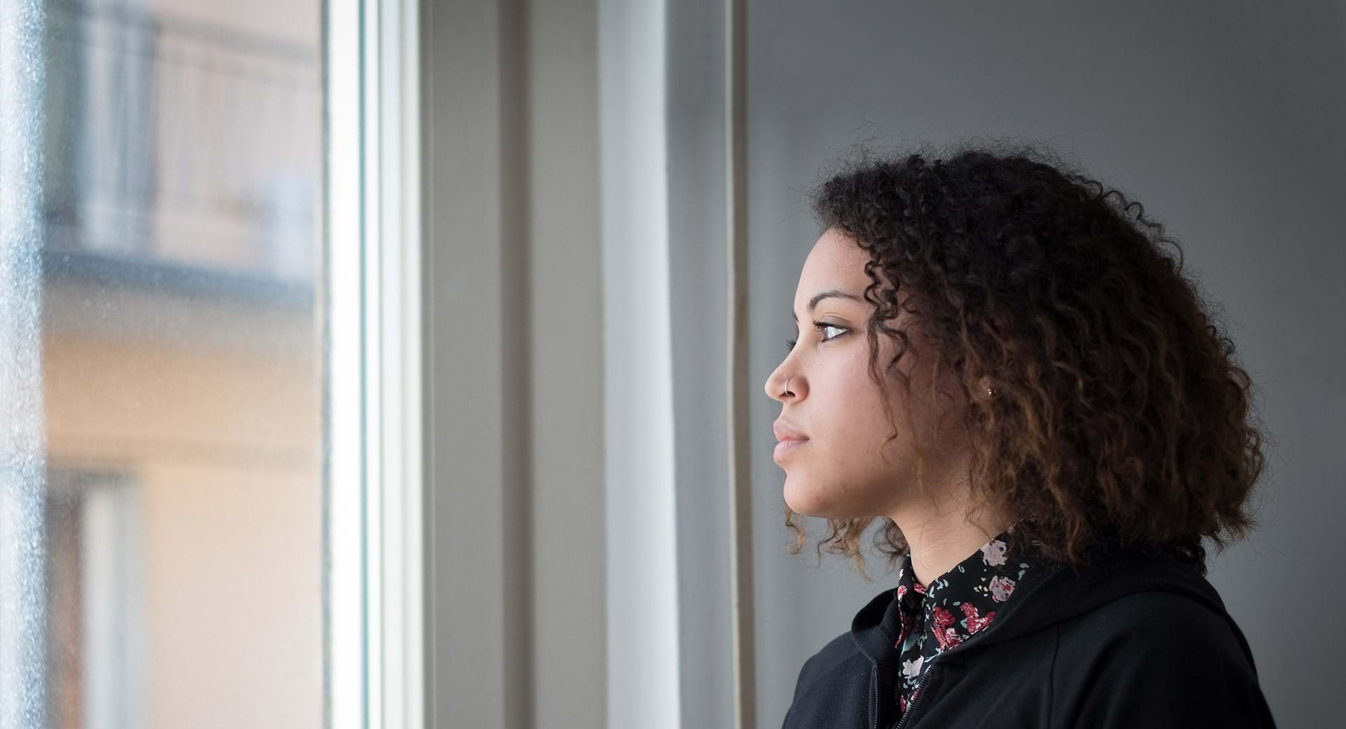 Young woman looks out of the window.