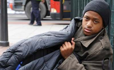 Homeless young man in a sleeping bag on the street.