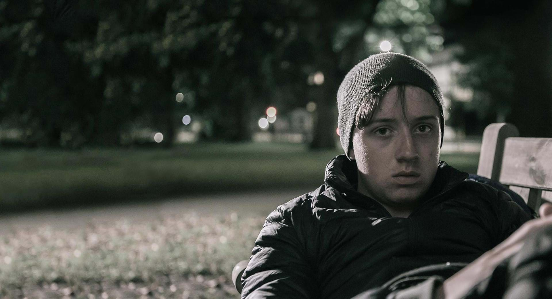 A boy sits on a park bench at nighttime.