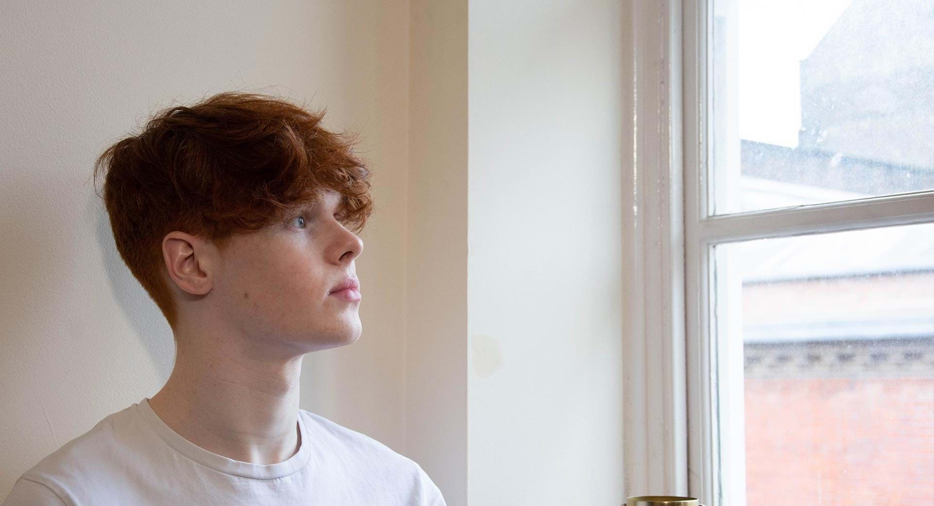 Teenage boy looks out of window