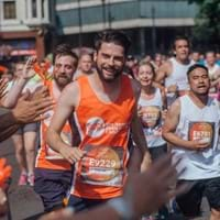 A smiling man runs an 10km race to raise money for Centrepoint and help homeless young people.