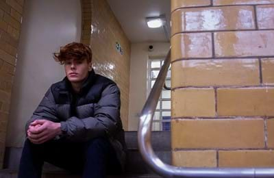 A teenage boy sits on stairs