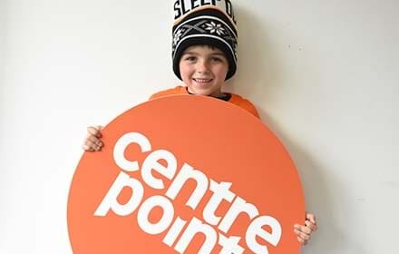 A boy holds up a Centrepoint sign.