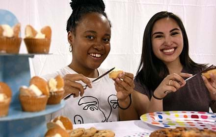 Two girls at a bake sale.