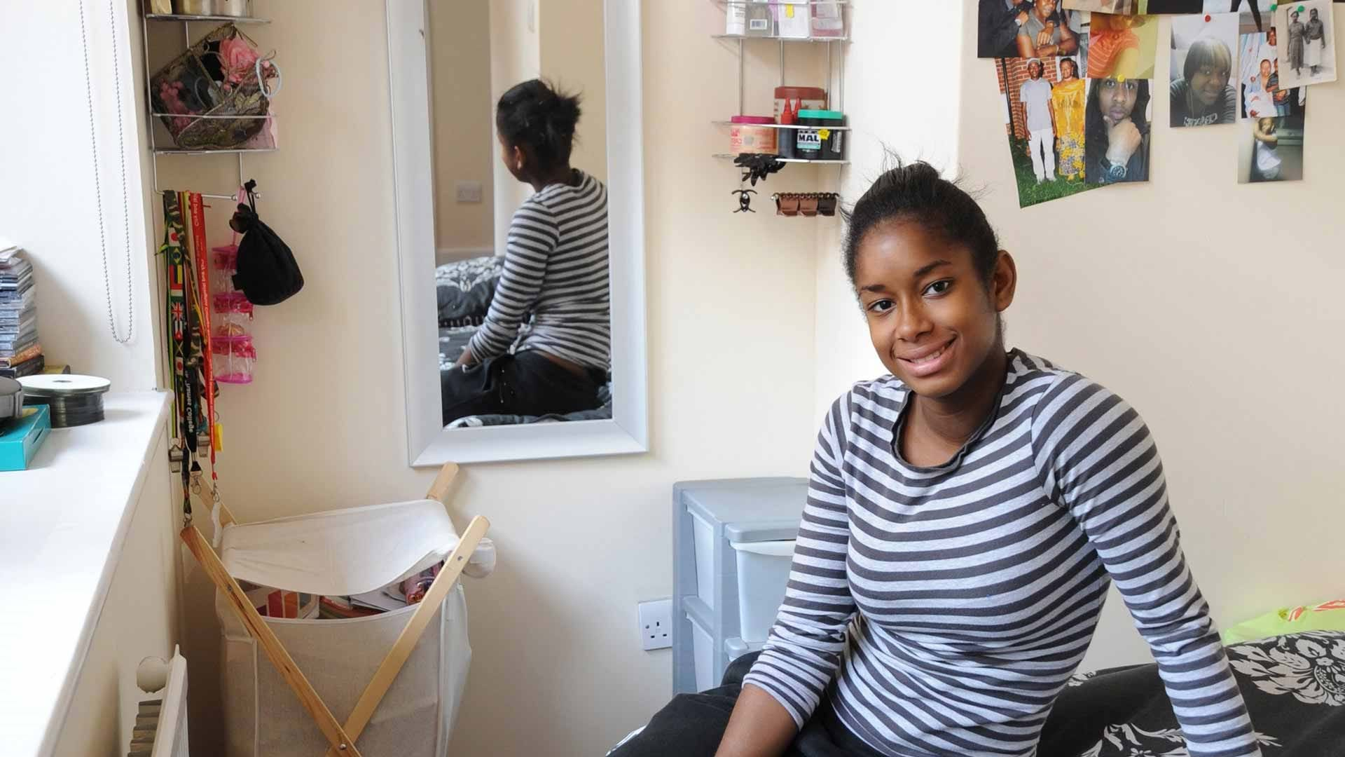 Smiling young woman sits on her bed