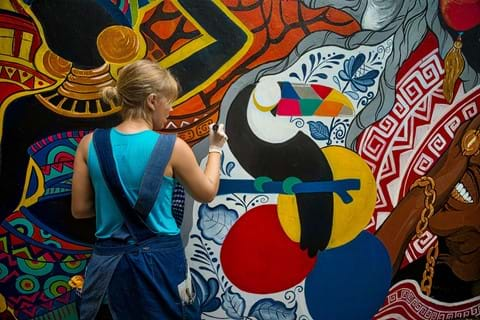 A young person painting a mural on a wall