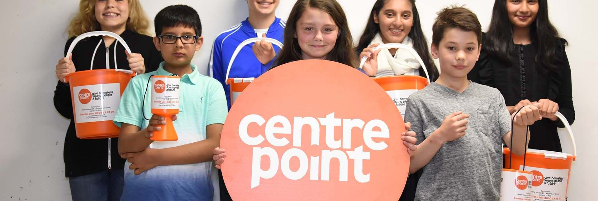 Schoolchildren hold up Centrepoint logos and buckets.