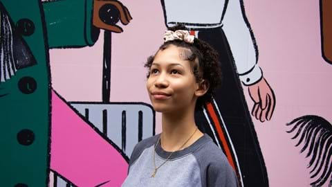 A young girl looks up positively in front of a wall of graffiti. With your help, we can help give homeless young people a future