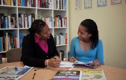 Happy young woman chats to a Centrepoint member of staff.