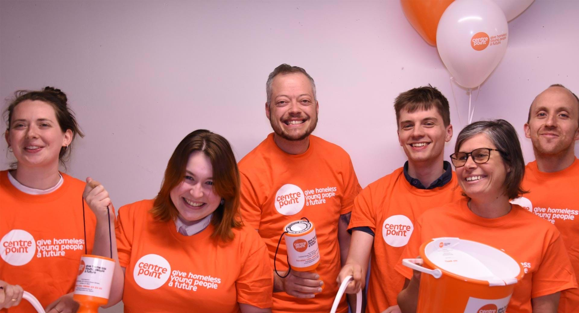 Centrepoint supporters hold up buckets and collection tins.