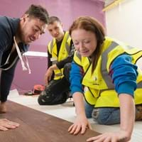 Young people learning to install flooring