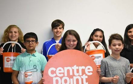 Children hold up Centrepoint buckets, collection tins and signs.