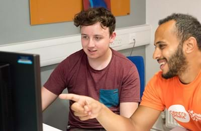 An image of a Centrepoint member of staff working with a homeless young person on a computer