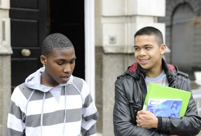 Two young males with school books