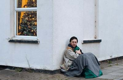 A homeless young man sitting on a street corner.